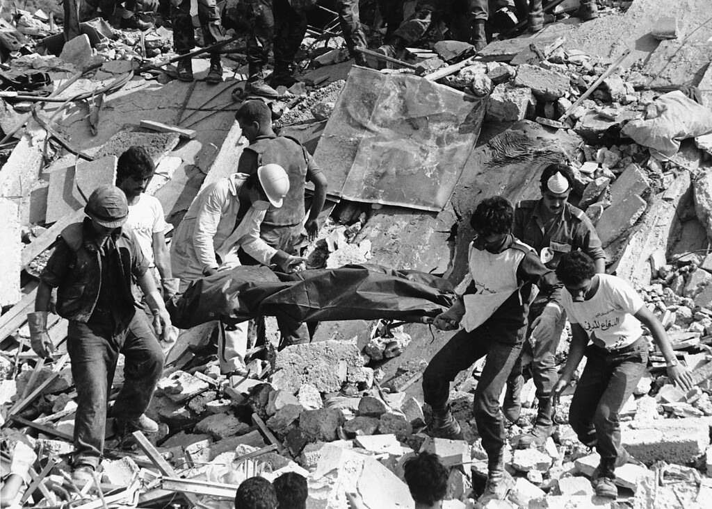 . In this Monday, Oct. 24, 1983, file photo, rescue workers are shown carrying the body of a U.S. Marine killed by the bombing of the Marine barracks in Beirut, Lebanon. The blast _ the single deadliest attack on U.S. forces abroad since World War II _ claimed the lives of 241 American service members.(AP Photo/Jamal, File)