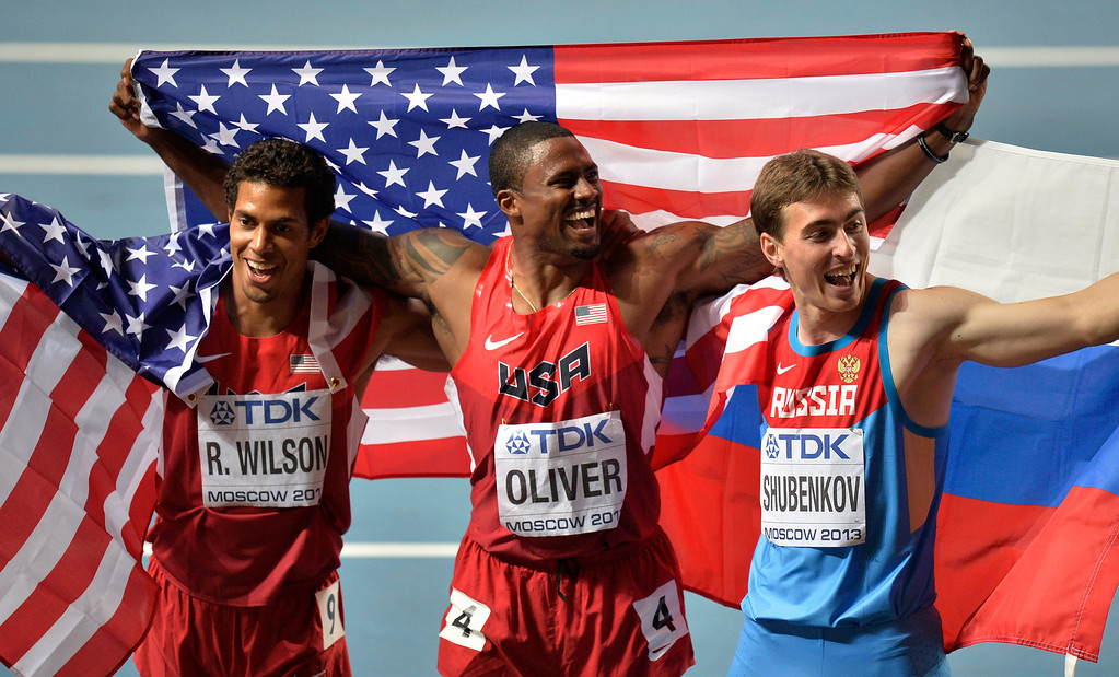 . USA\'s David Oliver, center, USA\'s Ryan Wilson, left, and Russia\'s Sergey Shubenkov celebrate after the men\'s 110-meter hurdles at the World Athletics Championships in the Luzhniki stadium in Moscow, Russia, Monday, Aug. 12, 2013. Oliver won gold, Wilson silver and Shubenkov bronze. (AP Photo/Martin Meissner)