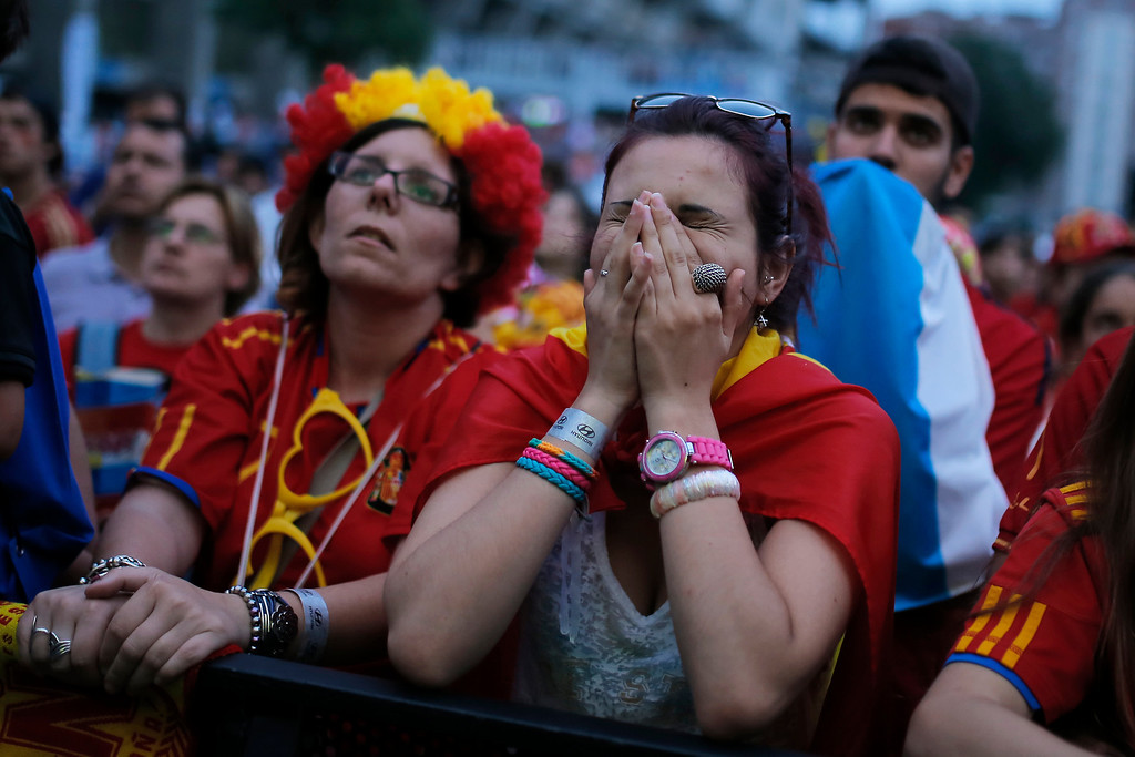 . Spanish soccer fans look on in dismay as they watch, on a giant screen, a World Cup soccer match between Spain and Chile, in Madrid, Spain, Wednesday, June 18, 2014. (AP Photo/Andres Kudacki)
