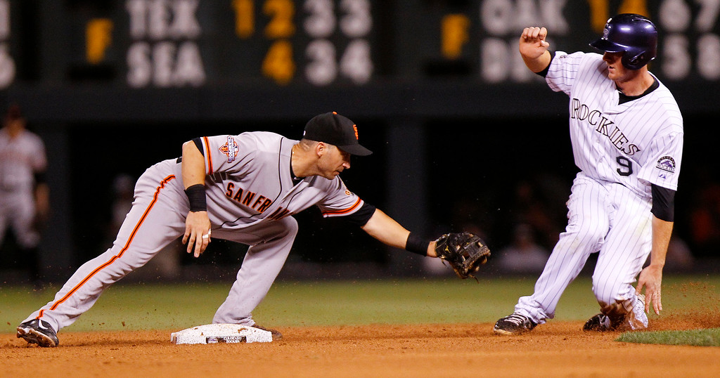 . San Francisco Giants\' Marco Scutaro, left, tags out Colorado Rockies\' DJ LeMahieu during the sixth inning of a baseball game, Wednesday, Aug. 28, 2013, in Denver. (AP Photo/Barry Gutierrez)