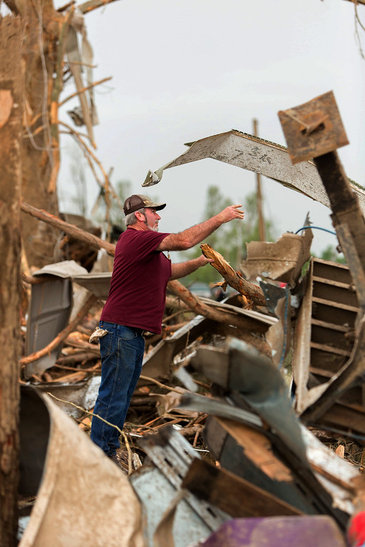 . Stanley Ray tosses a piece of scrap metal off of a debris pile Monday, April 28, 2014, while helping his brother clean up after a tornado struck his Vilonia, Ark., home late Sunday.  (AP Photo/Karen E. Segrave)
