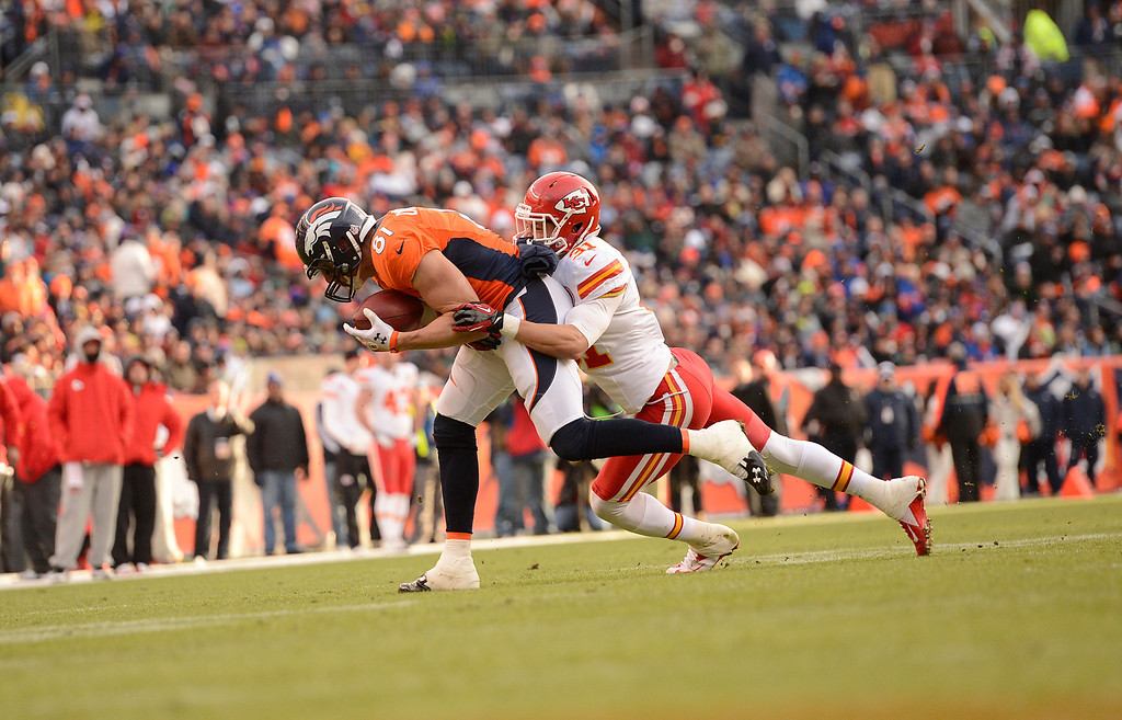 . Denver Broncos tight end Joel Dreessen (81) makes a catch and is tackled by Kansas City Chiefs free safety Tysyn Hartman (31) as the Denver Broncos took on the Kansas City Chiefs at Sports Authority Field at Mile High in Denver, Colorado on December 30, 2012. John Leyba, The Denver Post