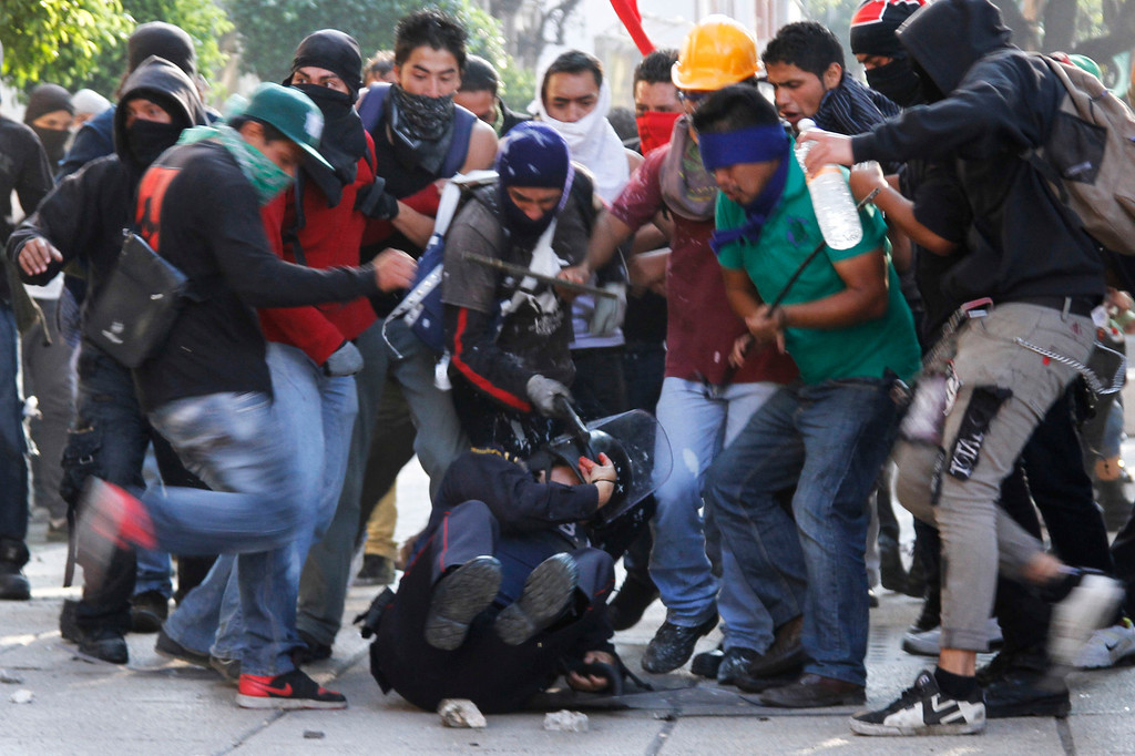 . Protesters attack a police officer during a march marking the anniversary of the Tlatelolco massacre in Mexico City, Wednesday, Oct. 2, 2013.  Mexico commemorated the 45th anniversary of the massacre of students holding an anti-government protest, killed by men with guns and soldiers in 1968 days before the Summer Olympics celebrations in Mexico City.  (AP Photo/Marco Ugarte)