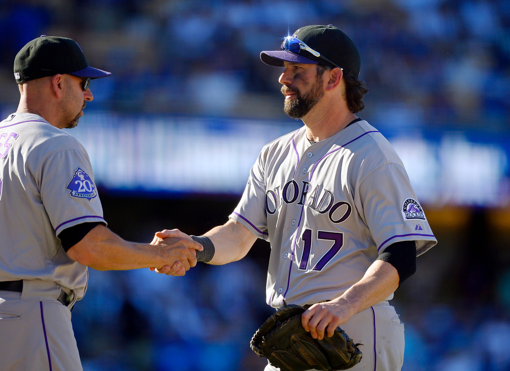 . Colorado Rockies manager Walt Weiss, left, shakes hands with Todd Helton after the Rockies defeated the Los Angeles Dodgers 2-1 in a baseball game, Sunday, Sept. 29, 2013, in Los Angeles. Helton was playing in the final game of his career. (AP Photo/Mark J. Terrill)