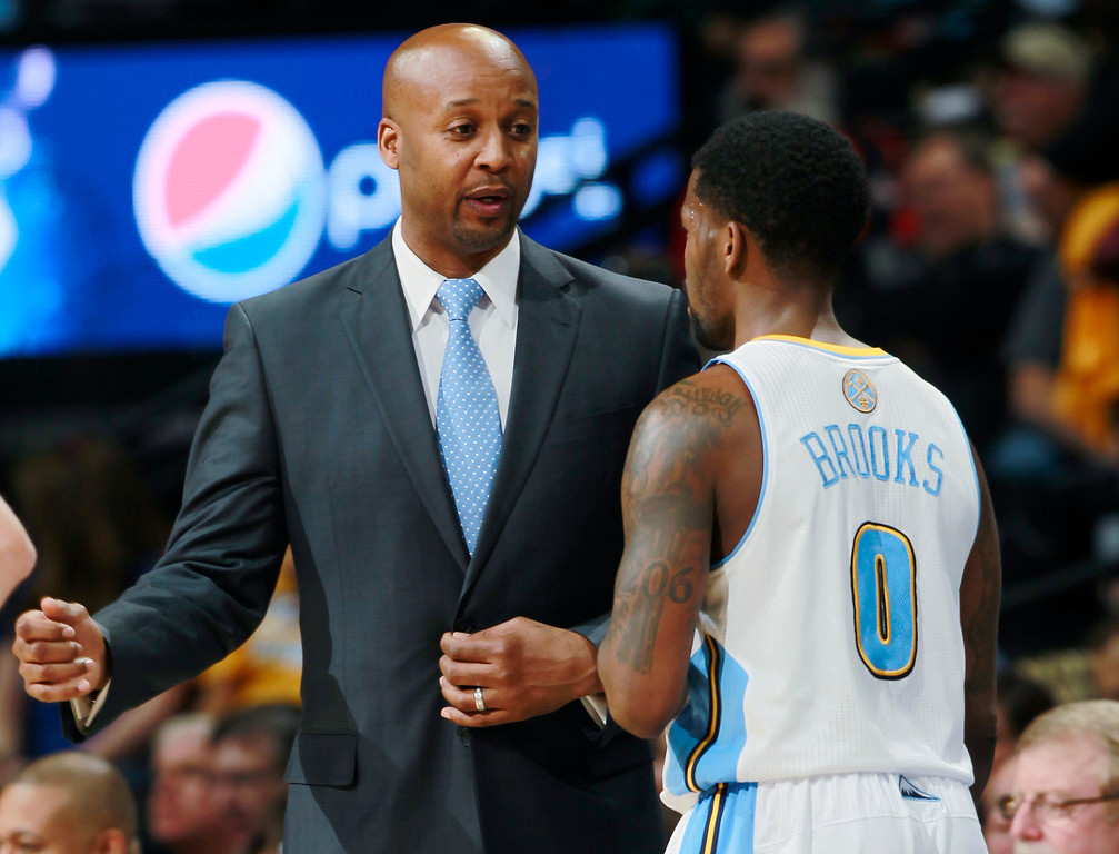 . Denver Nuggets head coach Brian Shaw, left, confers with guard Aaron Brooks during time out against the Houston Rockets in the first quarter of an NBA basketball game in Denver on Wednesday, April 9, 2014. (AP Photo/David Zalubowski)