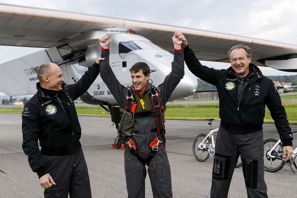 . (L to R) Swiss pilot Bertrand Piccard (L) and German test pilot Markus Scherdel and Swiss pilot Andre Borschberg pose in front of the solar-powered Solar Impulse 2 aircraft after its first flight on June 2, 2014 in Payerne.   AFP PHOTO / POOL / FABRICE COFFRINI/AFP/Getty Images