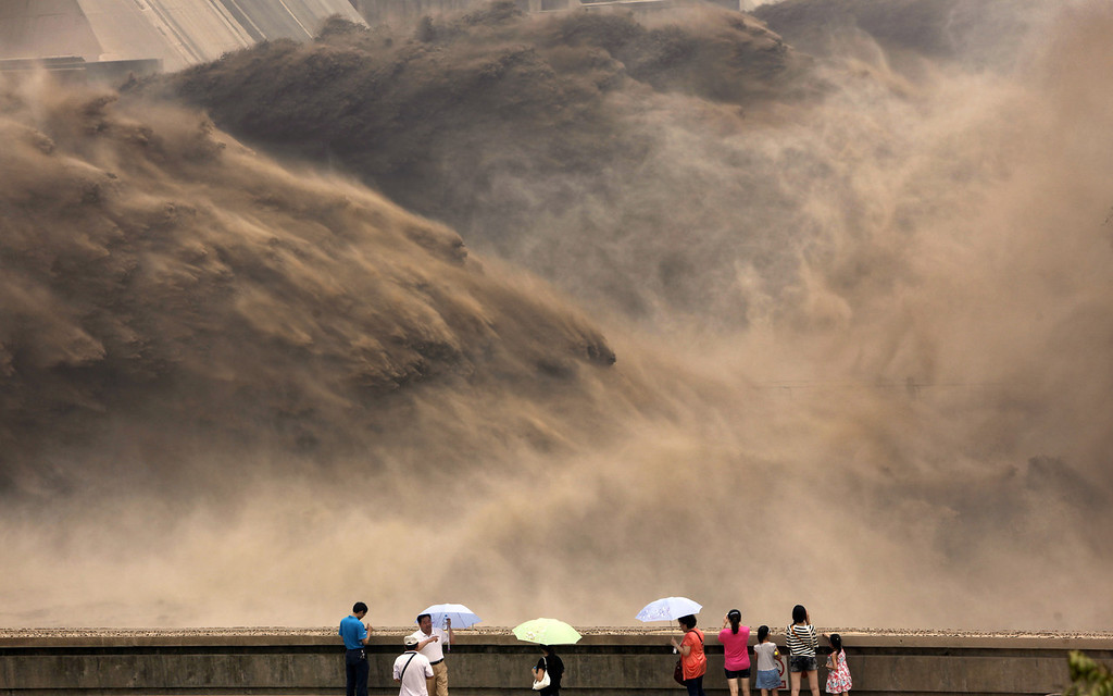 . This picture taken on July 6, 2012 shows visitors gathering to watch giant gushes of water being released from the Xiaolangdi dam to clear up the sediment-laden Yellow river and to prevent localized flooding, in Jiyuan, central China\'s Henan province. China is hit by big downpours every summer often causing fatalities as seen in 2010, which saw the nation\'s worst flooding in a decade leaving more than 4,300 people dead or missing. (STR/AFP/GettyImages)