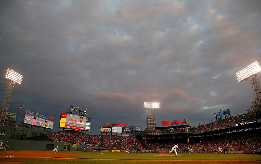 . Clouds over Fenway Park reflect light from the setting sun as Boston Red Sox starting pitcher John Lackey throws to a Tampa Bay Rays batter in the second inning in Game 2 of baseball\'s American League division series, Saturday, Oct. 5, 2013, in Boston. (AP Photo/Michael Dwyer)
