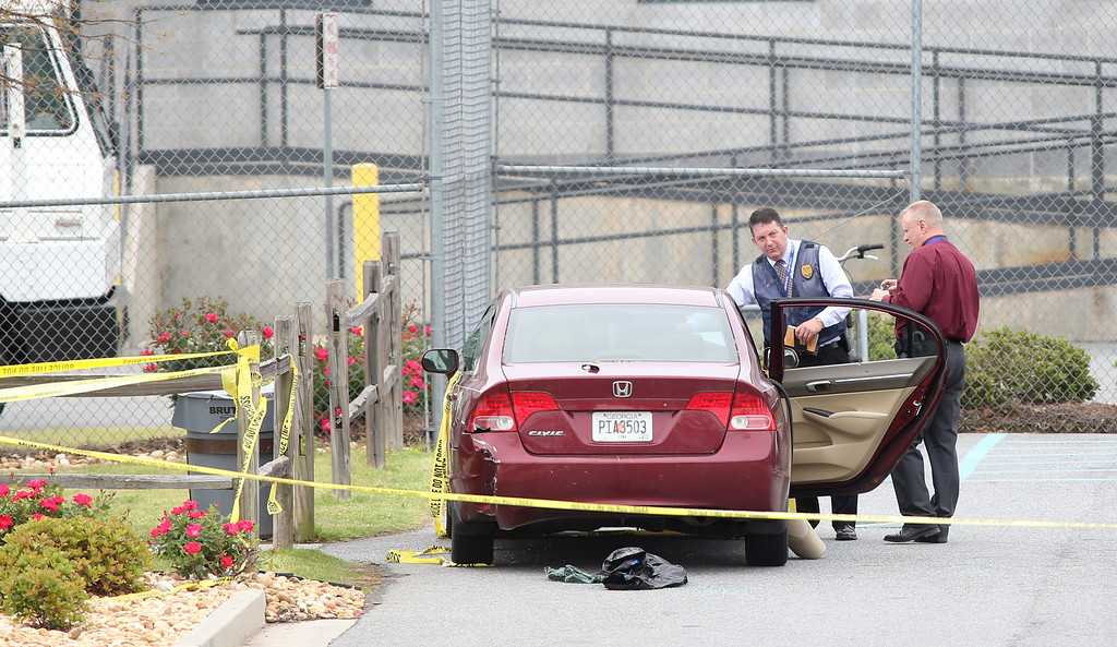 . Law enforcement officers works the scene after an early morning shooting at the Airport Road FedEx facility Tuesday April 29, 2014, in Kennesaw, Ga.  (AP Photo/Jason Getz)