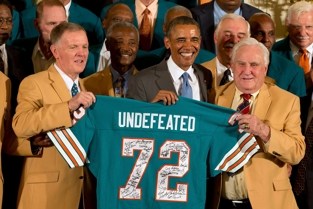 . Former Miami Dolphins football quarterback Bob Griese, left, President Barack Obama and 1972 Dolphins Coach Don Shula, right, hold a signed jersey in the East Room of the White House in Washington, Tuesday, Aug. 20, 2013, during a ceremony honoring the Super Bowl VII football Champion Miami Dolphins. The 1972 Miami Dolphins remain the only undefeated team in NFL history. Form left are, Griese, wide receiver Paul Warfield, the president, running back Larry Csonka and Shula. (AP Photo/Jacquelyn Martin)
