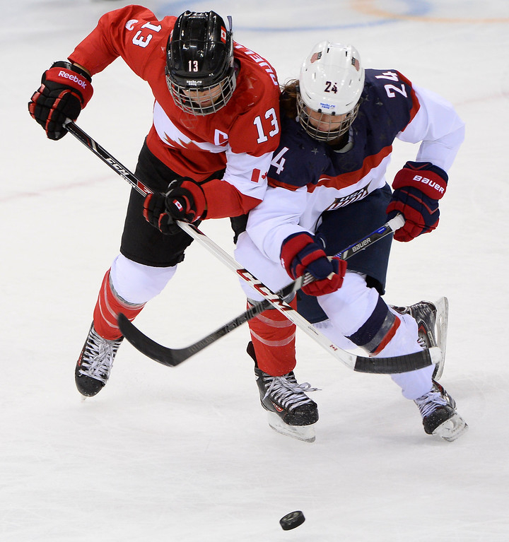 . Canada\'s Caroline Ouellette (L) vies for the puck with US Josephine Pucci during the Women\'s Ice Hockey Group A match between Canada and USA at the Sochi Winter Olympics on February 12, 2014 at the Shayba Arena. JONATHAN NACKSTRAND/AFP/Getty Images