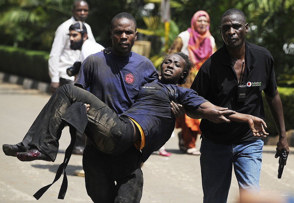 . A Kenyan woman is helped to safety after masked gunmen stormed an upmarket mall and sprayed gunfire on shoppers and staff, killing at least six on September 21, 2013 in Nairobi.  AFP PHOTO/SIMON  MAINA/AFP/Getty Images