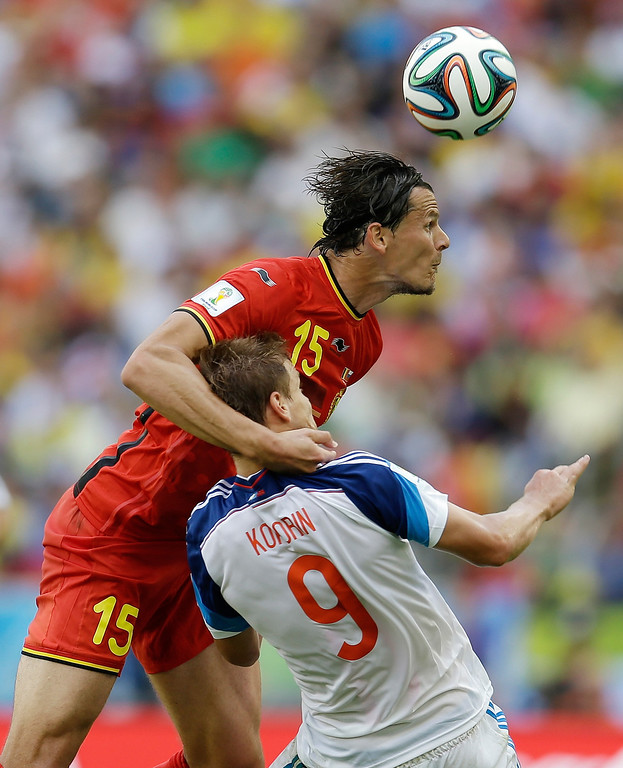 . Belgium\'s Daniel Van Buyten 915) hangs on to Russia\'s Alexander Kokorin (9) as he heads the ball during the group H World Cup soccer match between Belgium and Russia at the Maracana Stadium in Rio de Janeiro, Brazil, Sunday, June 22, 2014. (AP Photo/Natacha Pisarenko)