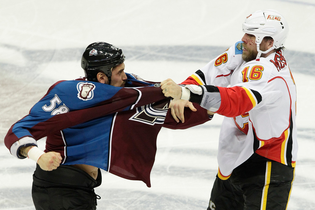 . Colorado Avalanches\' Patrick Bordeleau (58) and Calgary Flames\' Brian McGrattan (16) fight during the first period of an NHL hockey game on Friday, Nov. 8, 2013, in Denver. (AP Photo/Barry Gutierrez)