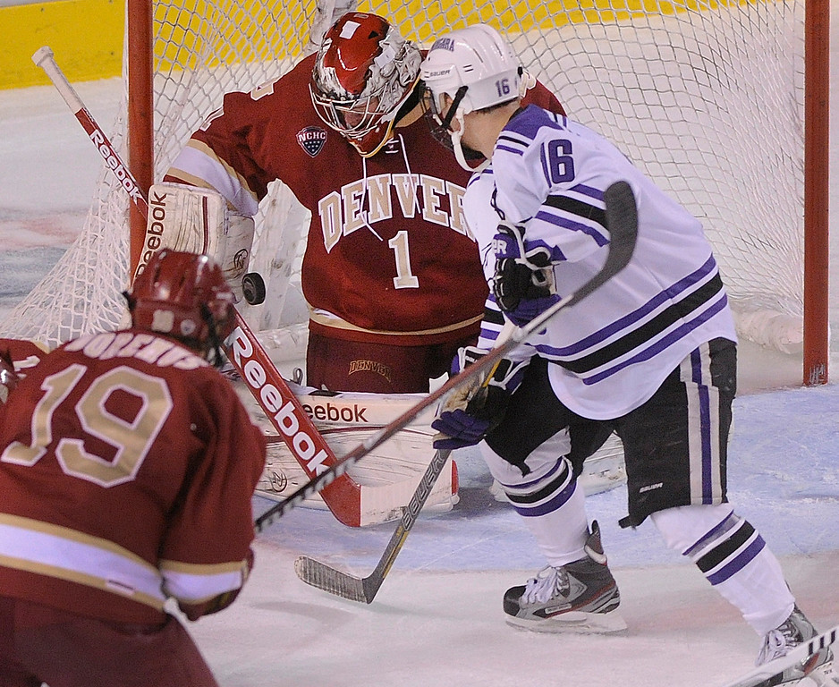 . DENVER, CO. - OCTOBER 25: Denver goaltender Sam Brittain (1) worked under pressure from Niagara center Chris Lochner (16) in the second period. The University of Denver hockey team hosted Niagara at Magness Arena Friday night, October 25, 2013. Photo By Karl Gehring/The Denver Post