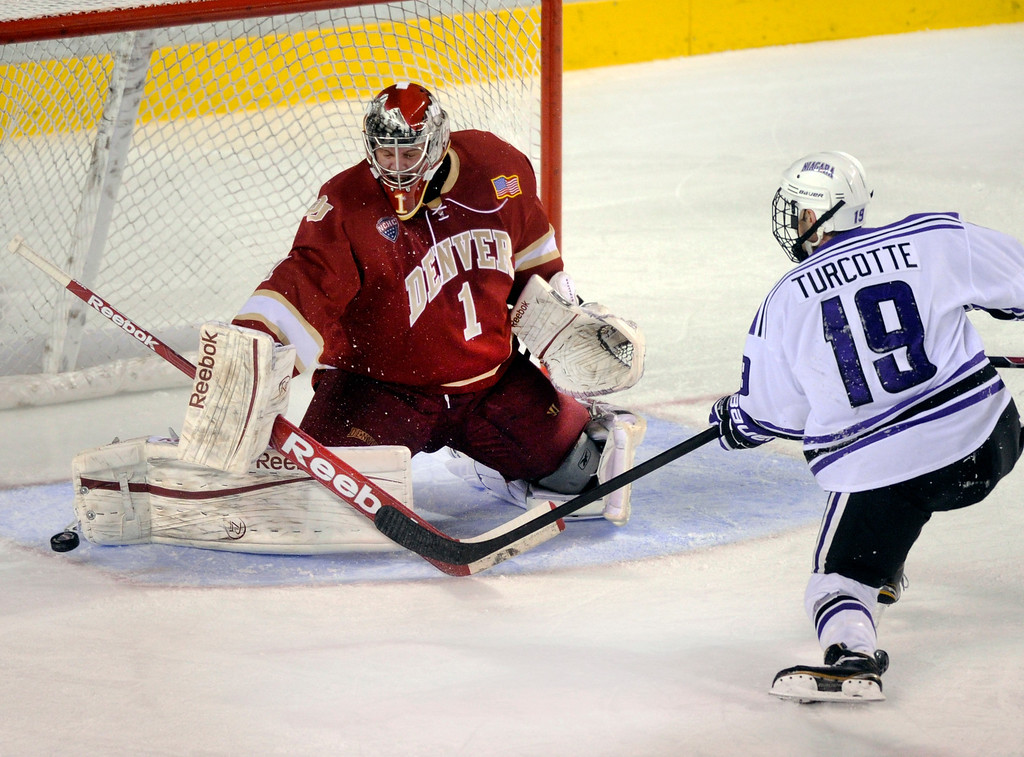 . DENVER, CO. - OCTOBER 25: Denver goalkeeper Sam Brittain (1) turned away a shot from Niagara center Hugo Turcotte (19) on a breakaway in the second period. The University of Denver hockey team hosted Niagara at Magness Arena Friday night, October 25, 2013. Photo By Karl Gehring/The Denver Post