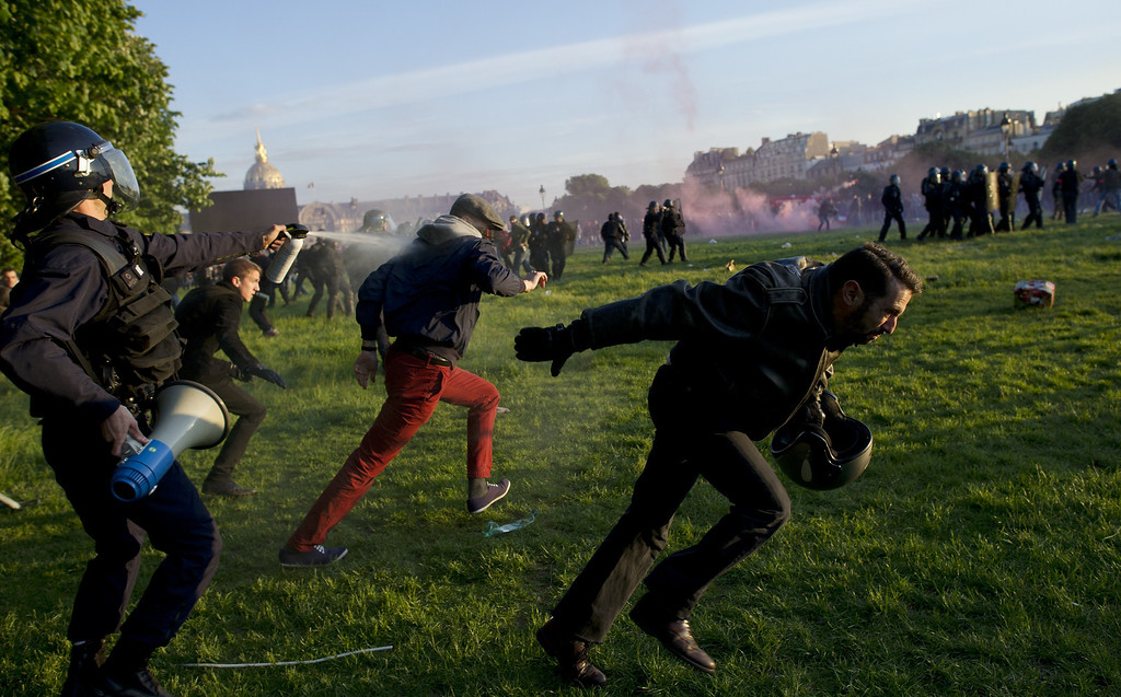 . A riot policeman sprays pepper spray at protesters on May 26, 2013 in Paris on the sidelines of demonstrations against a gay marriage law. France on May 18 became the 14th country to legalize same-sex marriage after President Francois Hollande signed the measure into law following months of bitter debate and demonstrations. Tens of thousands marched through Paris today to protest a new gay marriage law, with police on high alert amid warnings hardliners could infiltrate the demonstration and cause trouble.  FRED DUFOUR/AFP/Getty Images