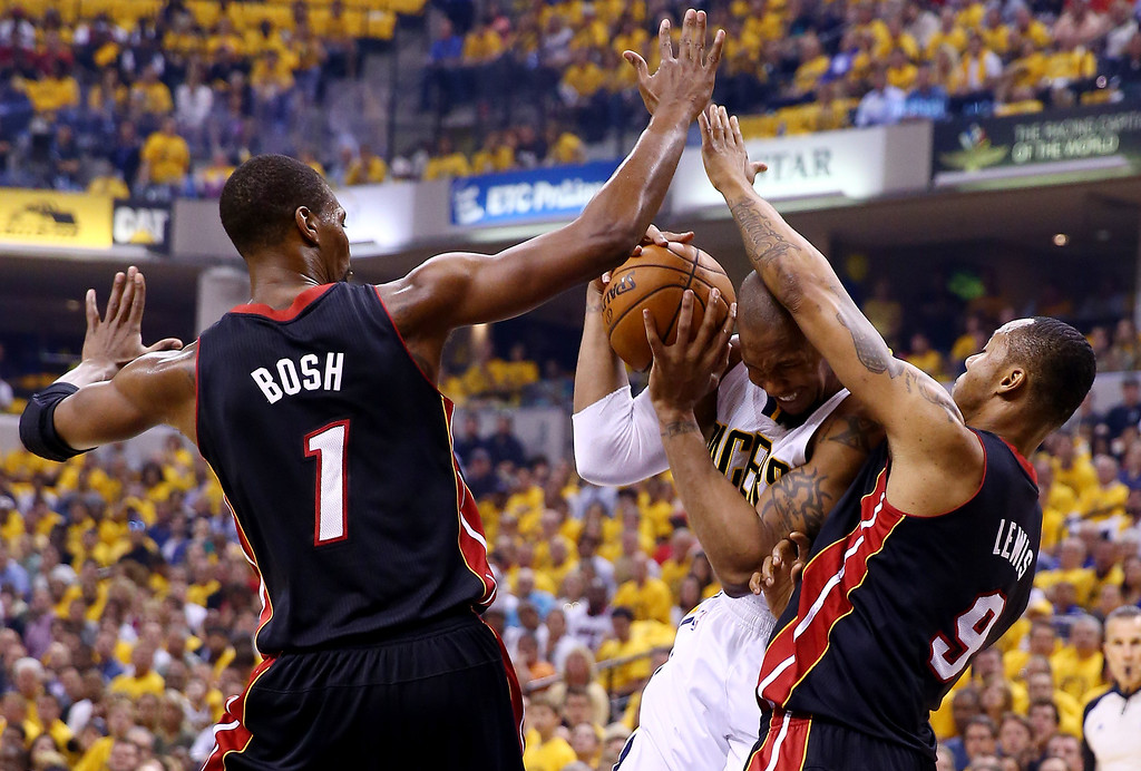 . INDIANAPOLIS, IN - MAY 28: David West #21 of the Indiana Pacers drives to the basket as Chris Bosh #1 and Rashard Lewis #9 of the Miami Heat defend during Game Five of the Eastern Conference Finals of the 2014 NBA Playoffs at Bankers Life Fieldhouse on May 28, 2014 in Indianapolis, Indiana.  (Photo by Andy Lyons/Getty Images)
