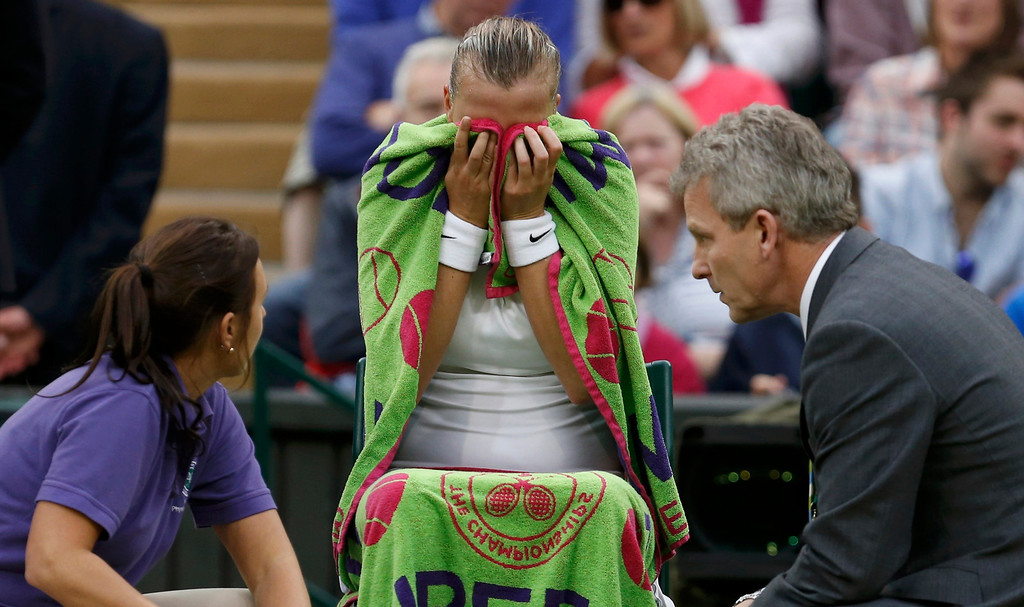 . Petra Kvitova of the Czech Republic receives medical attention during her women\'s quarter-final tennis match against Kirsten Flipkens of Belgium at the Wimbledon Tennis Championships, in London July 2, 2013.       REUTERS/Suzanne Plunkett