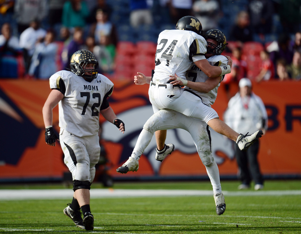 . From left, Monarch\'s Josh Hurst, Colin Hart and Ethan Marks celebrate Marks\' winning 1st down against Denver South 4A State Championship game at Sports Authority Field at Mile High on Saturday, Dec. 1, 2012. Monarch won 17-14. Hyoung Chang, The Denver Post