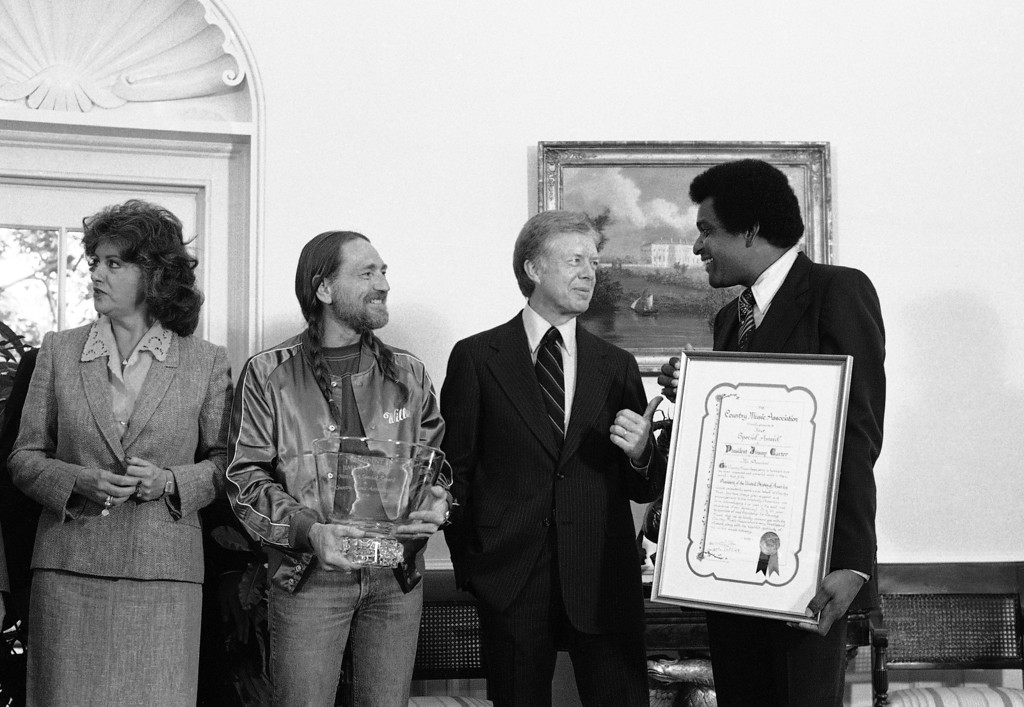 . President Jimmy Carter talks with country music singer Charley Pride, right, and entertainer Willie Nelson, second from left, in the Oval Office at the White House in Washington, May 16, 1979 after the two presented him with a special country music award for his support of country music.  Woman at left is unidentified.  (AP Photo/Harvey Georges)