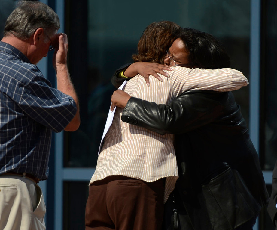 """. Arlene Holmes is hugged by Sherry Delaney as she prays in her ear after the James Holmes hearing at the Arapahoe County Justice Center. Delaney and her family rode the elevator down with the Holmes\' and her great granddaughter 4 month old Sariah smiled at Arleen Holmes. Delaney said \""""You feel the love, your surrounded by the love,\"""" and Holmes started to cry. When they got outside Delaney asked Holmes if she could pray for her \""""I could see she was broken,\"""" she said. I didn\'t know who she was at the time but I would have prayed with no matter what, that\'s what we do,\"""" she said. Delaney lives just down the street from the theater and heard the commotion that night. April 01, 2013 Centennial, Colorado. (Photo By Joe Amon/The Denver Post)"""