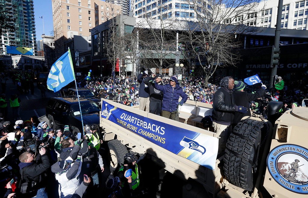 . Seattle Seahawks quarterback Russell Wilson, center, waves to fans during the Super Bowl champions parade on Wednesday, Feb. 5, 2014, in Seattle. (AP Photo/Ted S. Warren)