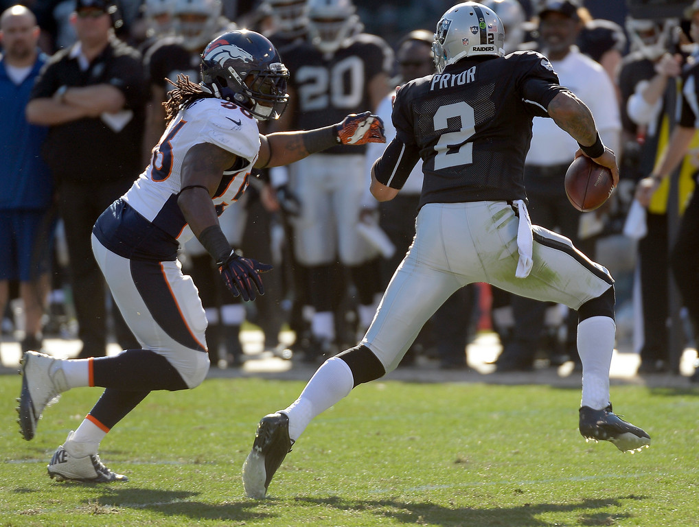 . Oakland Raiders quarterback Terrelle Pryor (2) gets chased down by Denver Broncos outside linebacker Nate Irving (56) for a sack during the first quarter at O.co Coliseum. (Photo by John Leyba/The Denver Post)