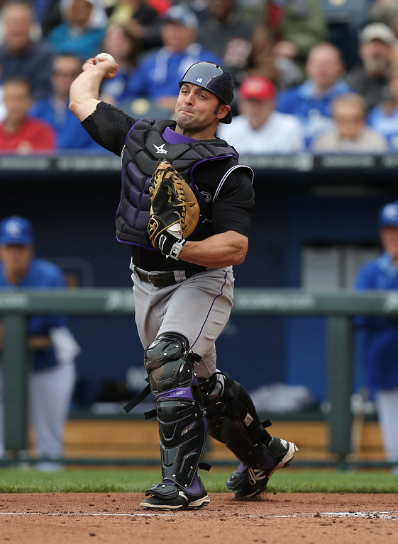 . KANSAS CITY, MO - MAY 14:  Michael McKenry #8 of the Colorado Rockies throws to third to get the out on Mike Moustakas of the Kansas City Royals who was trying to steal in the second inning at Kauffman Stadium on May 14, 2014 in Kansas City, Missouri. (Photo by Ed Zurga/Getty Images)