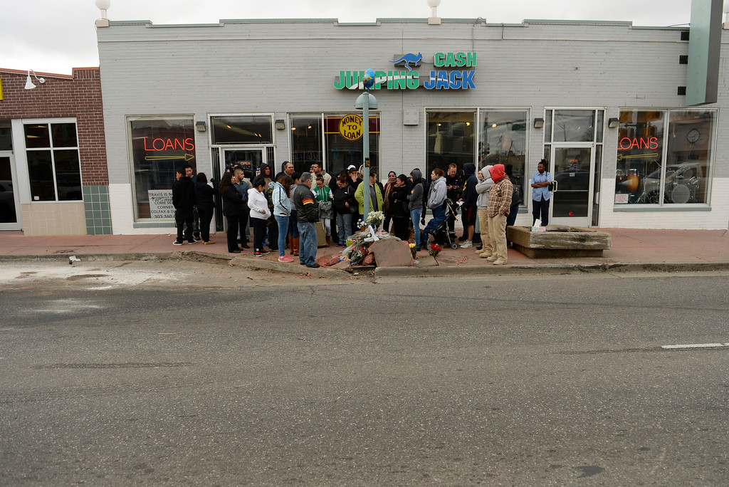 . Friends and family gather at the corner of East Colfax Avenue and Dayton Street in Aurora where Juan Carlos Dominguez-Palomino was killed earlier in a fatal crash, Monday, March 24, 2014.  (Photo by RJ Sangosti/The Denver Post)
