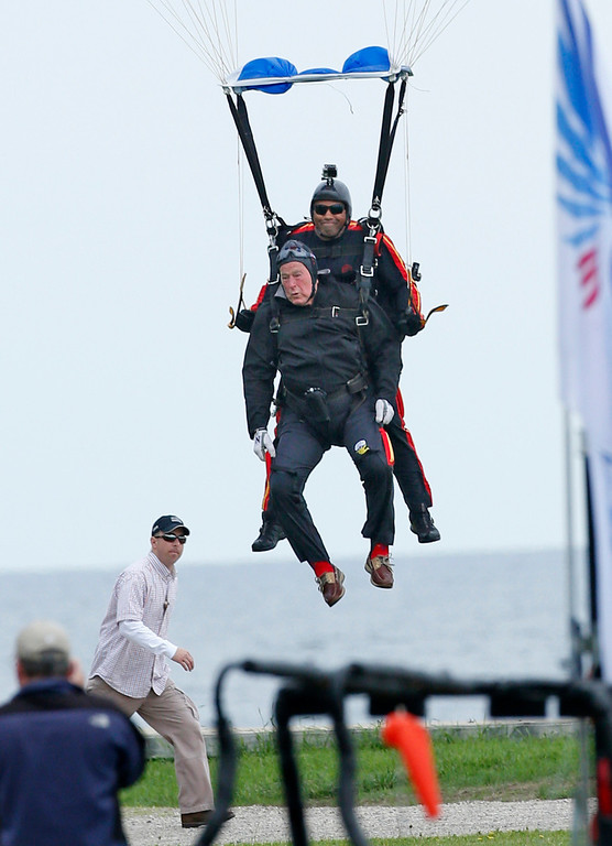 . Former President George H.W. Bush, strapped to Sgt. 1st Class Mike Elliott, a retired member of the Army\'s Golden Knights parachute team, prepare to land on the lawn at St. Anne\'s Episcopal Church while celebrating Bush\'s 90th birthday in Kennebunkport, Maine, Thursday, June 12, 2014. (AP Photo/Robert F. Bukaty)