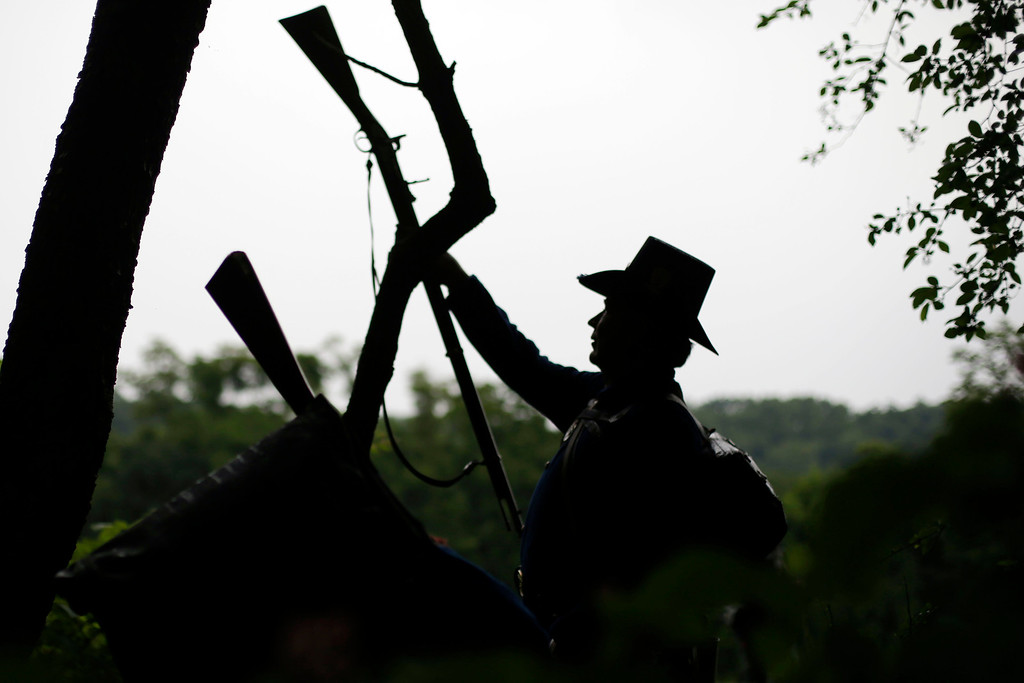 . A member of the Union Army\'s Murray\'s Brigade slings his weapon on a tree as he and others set up camp under threatening sky during ongoing activities commemorating the 150th anniversary of the Battle of Gettysburg, Thursday, June 27, 2013, in Gettysburg, Pa. (AP Photo/Matt Rourke)