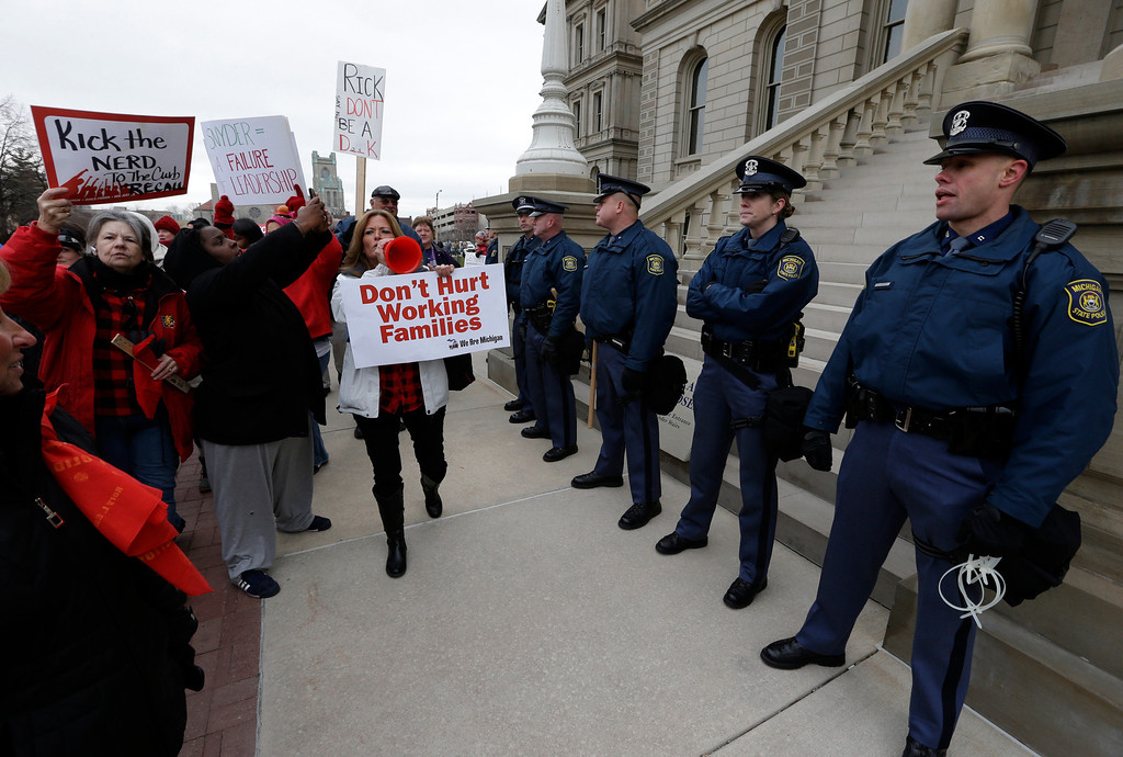 . Protesters gather for a rally at the State Capitol in Lansing, Mich., Tuesday, Dec. 11, 2012. The crowd is protesting right-to-work legislation passed last week. Michigan could become the 24th state with a right-to-work law next week. Rules required a five-day wait before the House and Senate vote on each other\'s bills; lawmakers are scheduled to reconvene Tuesday and Gov. Snyder has pledged to sign the bills into law. (AP Photo/Paul Sancya)