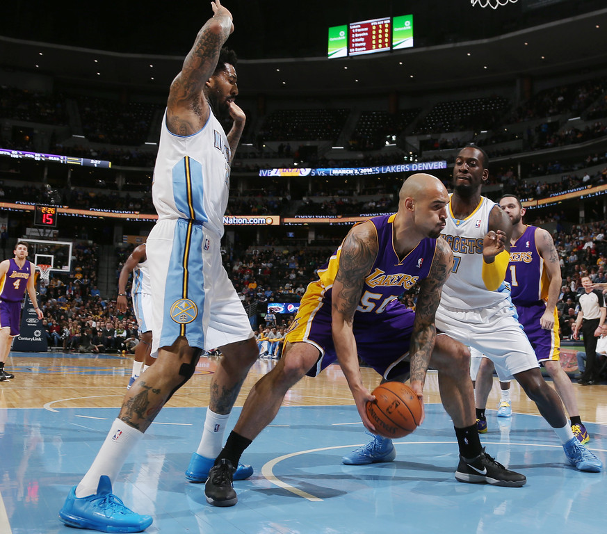 . Los Angeles Lakers center Robert Sacre, center, picks up loose ball as Denver Nuggets forwards Wilson Chandler, left, and J.J. Hickson cover in the first quarter of an NBA basketball game in Denver on Friday, March 7, 2014. (AP Photo/David Zalubowski)