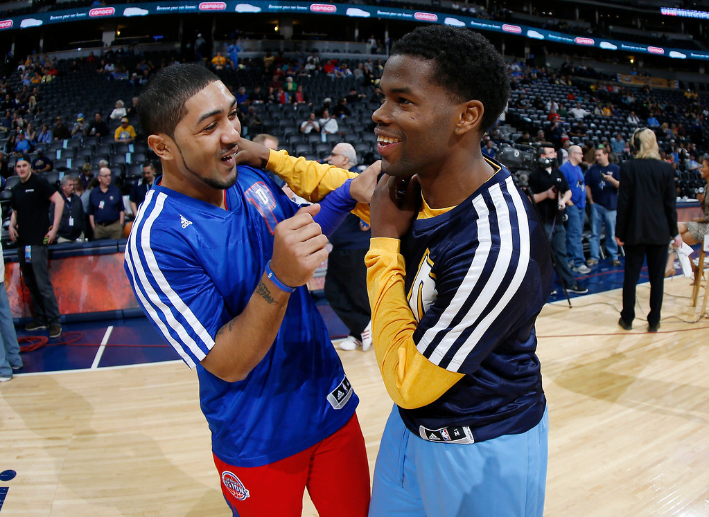 . Detroit Pistons guard Peyton Siva, left, jokes with Denver Nuggets guard Aaron Brooks before the first quarter of an NBA basketball game in Denver on Wednesday, March 19, 2014. (AP Photo/David Zalubowski)