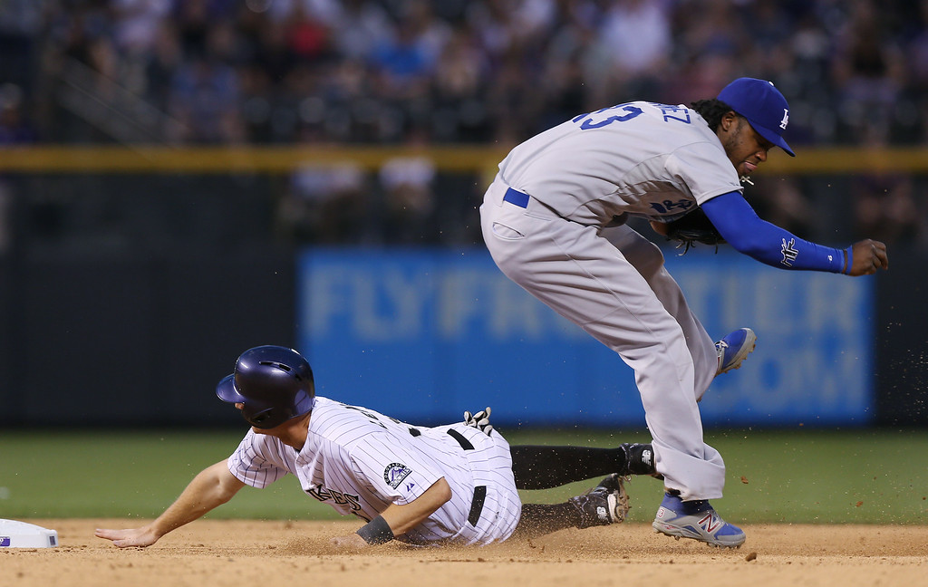 . Los Angeles Dodgers shortstop Hanley Ramirez, right, jumps over Colorado Rockies\' DJ LeMahieu after forcing him out at second base on the front end of a double play hit into by pinch-hitter Brandon Barnes to end the seventh inning of the Dodgers\' 3-2 victory in a baseball game in Denver on Thursday, July 3, 2014. (AP Photo/David Zalubowski)