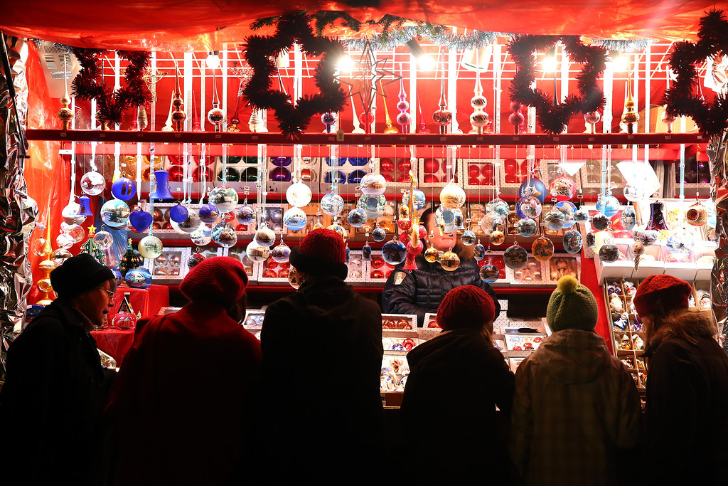 . Visitors gather at a stand to see traditional Christmas ornaments   at the annual Christmas market at Marienplatz and the Town Hall on its opening day on November 25, 0213 in Munich, Germany.  (Photo by Alexander Hassenstein/Getty Images)