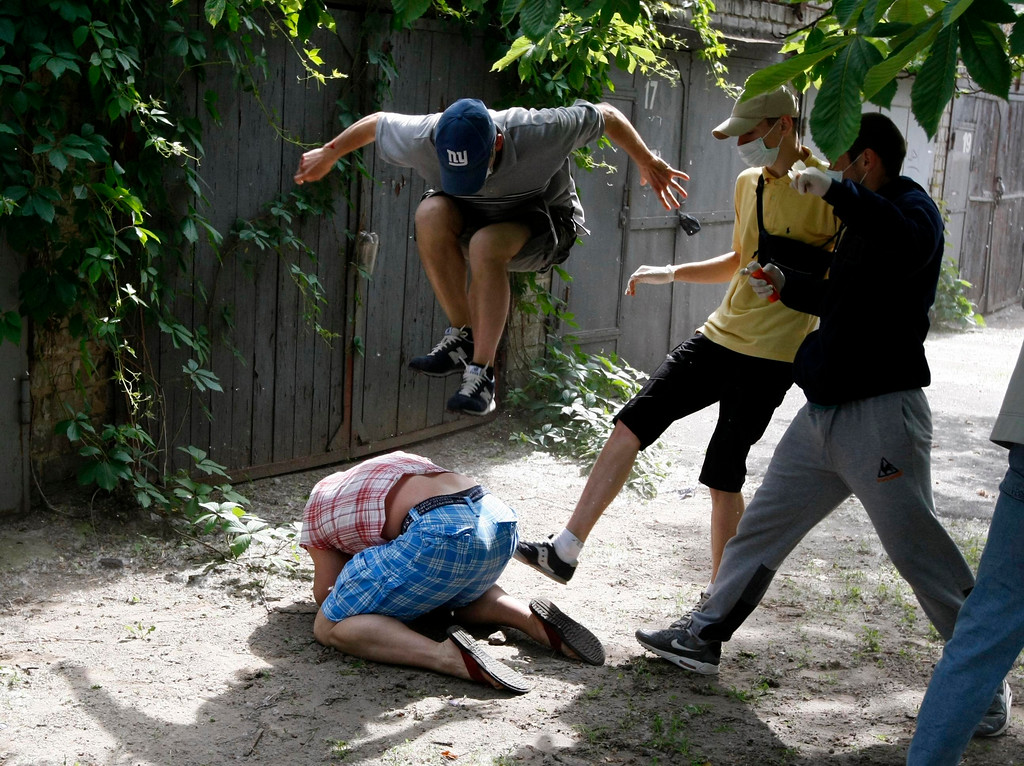 . Unidentified people beat Svyatoslav Sheremet (L, bottom), head of Gay-Forum of Ukraine public organization, in Kiev, May 20, 2012. Sheremet was attacked after meeting with members of the media to inform them that a scheduled gay parade was cancelled. The attackers ran off when they realised members of the media were documenting the attack.  REUTERS/Anatolii Stepanov