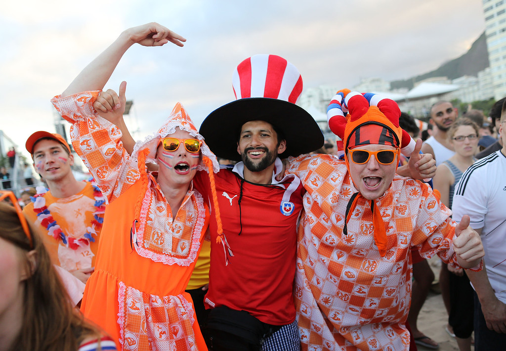 . Dutch soccer fans pose for a photo with a Chilean soccer fan, center, while watching the live broadcast of the World Cup match between Spain and the Netherlands, inside the FIFA Fan Fest area on Copacabana beach in Rio de Janeiro, Brazil, Friday, June 13, 2014. The Netherlands thrashed Spain 5-1 Friday. It was a humiliating defeat for the defending World Cup champions. (AP Photo/Leo Correa)