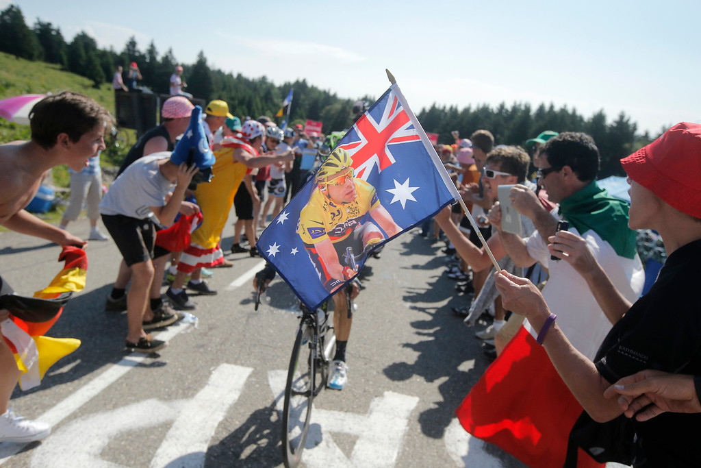 . A fan of Australia\'s Cadel Evans waves an Australian flag bearing his image with the overall leader\'s yellow jersey as riders pass during the 20th stage of the Tour de France cycling race over 125 kilometers (78.1 miles) with start in in Annecy and finish in Annecy-Semnoz, France, Saturday July 20 2013. (AP Photo/Laurent Cipriani)