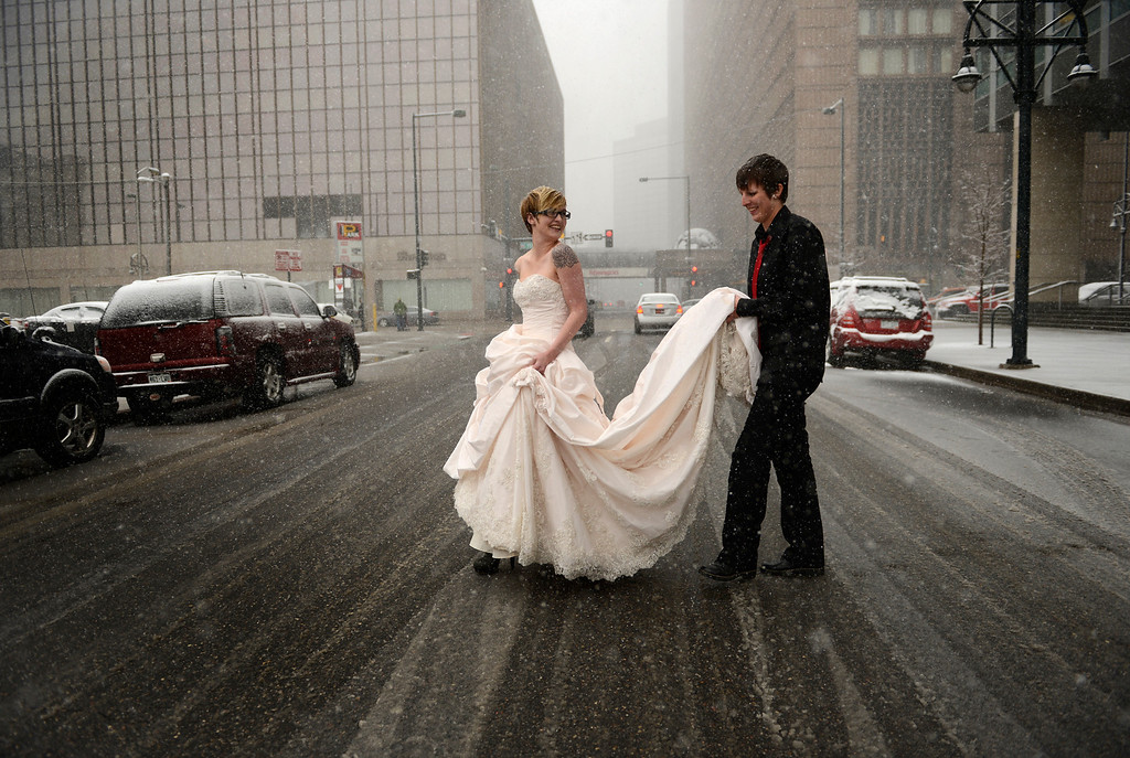 . DENVER, CO-May 01, 2013: Erin Ivie, 23, left, and her partner Kristyn Lindstrom, 25, leave to do wedding photos, outside in the snow, after their civil-union  ceremony in downtown Denver, May 01, 2013.  Hundreds of Colorado gay and lesbian couples put an official government seal on their relationships. (Photo By RJ Sangosti/The Denver Post)