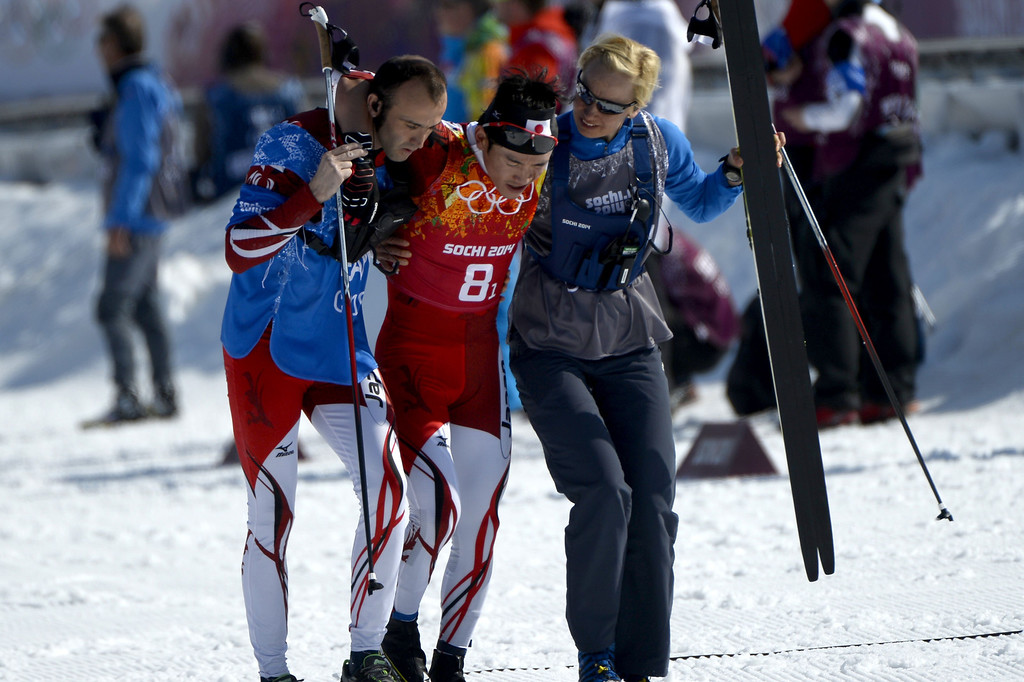 . Japan\'s Hiroyuki Miyazawa is helped after competing in the first relay of the Men\'s Cross-Country Skiing 4 x 10km Relay at the Laura Cross-Country Ski and Biathlon Center during the Sochi Winter Olympics on February 16, 2014 in Rosa Khutor near Sochi. PIERRE-PHILIPPE MARCOU/AFP/Getty Images