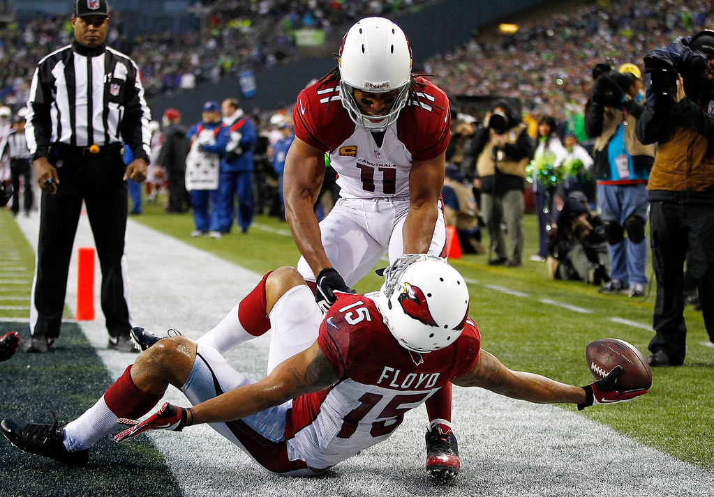. Michael Floyd #15 of the Arizona Cardinals celebrates a touchdown with Larry Fitzgerald #11 against the Seattle Seahawks on December 22, 2013 at CenturyLink Field in Seattle, Washington.  (Photo by Jonathan Ferrey/Getty Images)