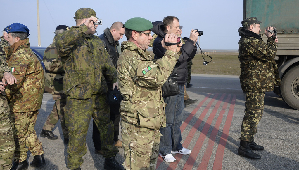 . OSCE military observers take photos during negotiations with pro-Russian soldier forces at the Chongar check point blocking the entrance to Crimea on March 7, 2014. Two buses carrying OSCE observers trying to enter Crimea turned back Friday after being blocked by armed men at a checkpoint, an AFP reporter said. Two sources within the mission said the team of 47 military and civilian observers was returning to the Ukrainian city of Kherson where they had spent the night after being similarly blocked on Thursday. ALEXANDER NEMENOV/AFP/Getty Images