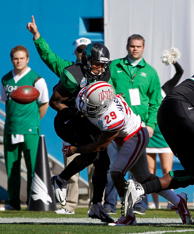 . North Texas wide receiver Carlos Harris, left, fumbles the ball as he is hit by UNLV defensive back Tajh Hasson (29) during the first half of the Heart of Dallas NCAA college football game, Wednesday, Jan. 1, 2014, in Dallas. North Texas recovered the ball.  (AP Photo/Mike Stone)