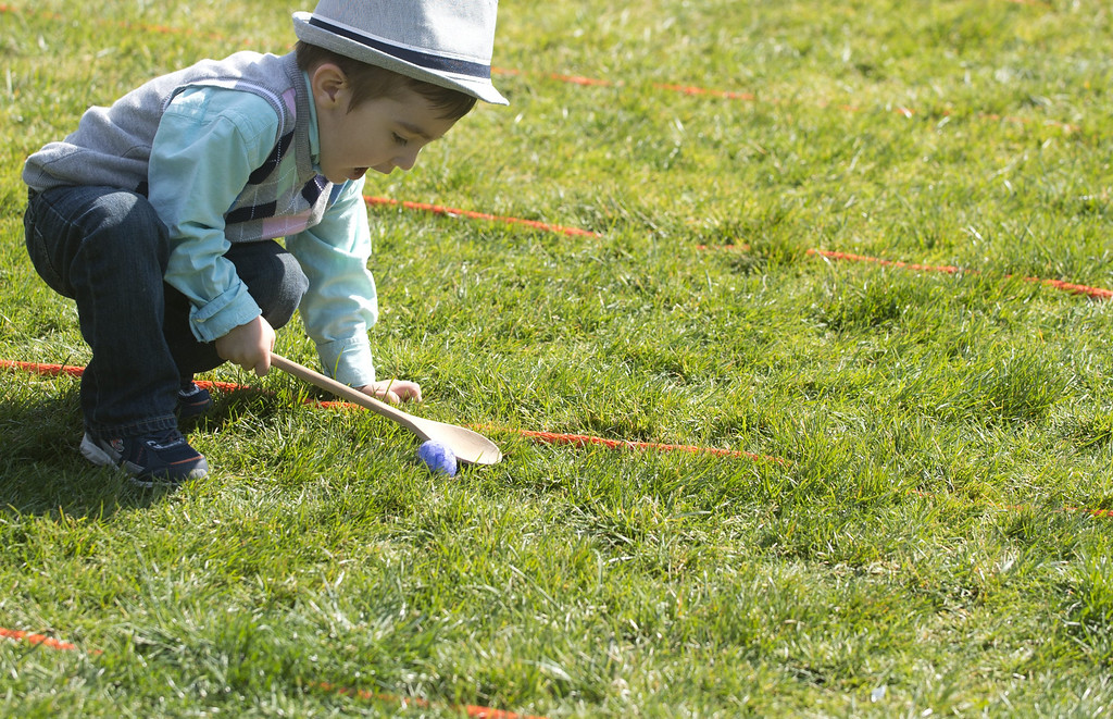 . A young boy races with an egg on a spoon during the White House Easter Egg Roll on the South Lawn of the White House in Washington, DC, April 1, 2013. US President Barack Obama hosts the annual event, featuring live music, sports courts, cooking stations, storytelling and Easter egg rolling. AFP PHOTO / Saul LOEB/AFP/Getty Images