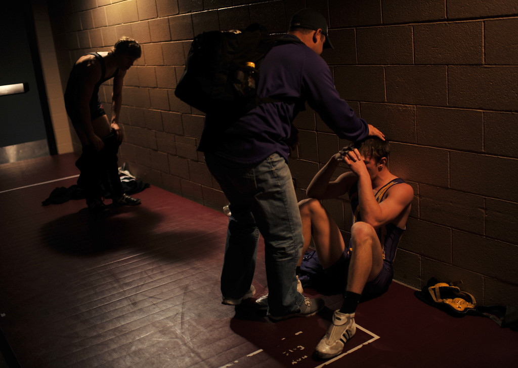 . DENVER, CO. - FEBRUARY 22: Coach Dustin Uhland of Eads High School, front right, comforts Blaine Winder of 145 pound class after Winder\'s losing preliminary matches of 2A State Championship tournament at Pepsi Center February 22, 2013. Denver, Colorado. (Photo By Hyoung Chang/The Denver Post)