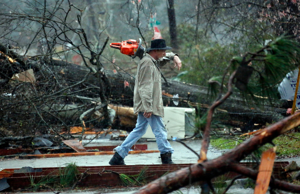 . A Hattiesburg, Miss., resident walks through a tornado damaged neighborhood Monday, Feb. 11, 2013, after cutting away branches blocking a senior citizen\'s entrance to her home following a Sunday afternoon tornado that caused damage throughout the South Mississippi college town. (AP Photo/Rogelio V. Solis)