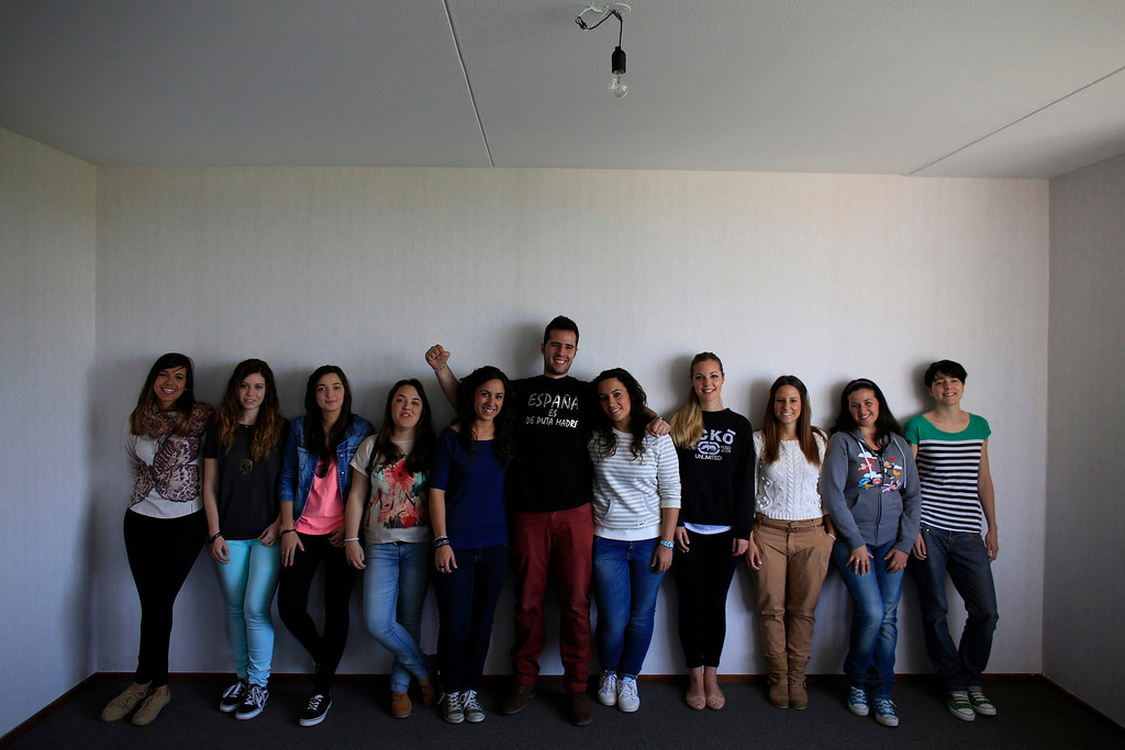 """. (L-R) Spanish nurses Sara Vallejo, 22, Maria Grifo, 23, Pilar Baldayo, 23, Marta Martinez, 24, Maria Jose Marin, 23, Alberto Soto, 24, Maria Teresa Marin, 23, Vanesa Diaz, 22, Estefania Torrico, 27, Angelica Munoz, 29 and Angie Luque, 25, pose for a portrait in an apartment in the Deo Gratias nursing home in The Hague, June 8, 2013. After months of studying Dutch, a group of young Spanish nurses moved to the Netherlands to take up work, fleeing a dismal job market at home. Spain\'s population dropped last year for the first time on record as young professionals and immigrants who moved here during a construction boom head for greener pastures. Spain\'s jobless rate is 27 percent, and more than half of young workers are unemployed. For Spanish nurses, the Netherlands\' nursing deficit is a boon. Soto\'s t-shirt reads: \""""Spain is bloody wonderful\"""". Picture taken June 8, 2013.  REUTERS/Marcelo del Pozo"""