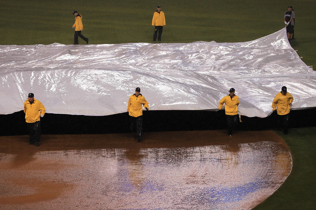 . DENVER, CO - JULY 27:  The tarp is placed on the infield as rain halts the game with the Milwaukee Brewers leading the Colorado Rockies 7-5 in the bottom of the ninth inning at Coors Field on July 27, 2013 in Denver, Colorado.  (Photo by Doug Pensinger/Getty Images)